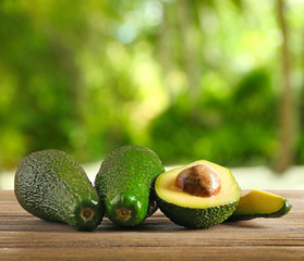 Fresh avocados on wooden table. Blurred green background.