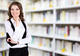 Young woman on blurred bookshelves background. Law concept.