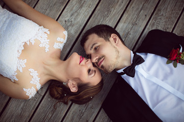 Beautiful bride and groom enjoy a sunny day while lying down on