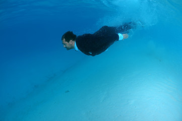The groom in a suit dives into the underwater, Indian Ocean, Maldives