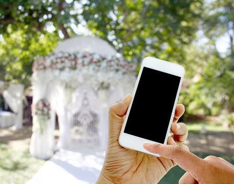 hand hold and touch screen smart phone on wedding tent blurred b