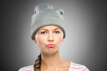 Upset young woman in winter hat