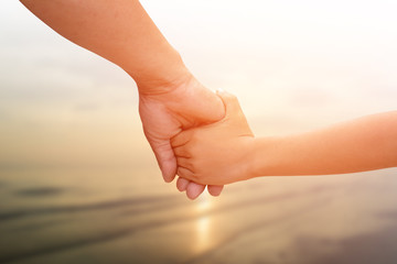 Father hand in hand son.Blurred background sunset over the sea.