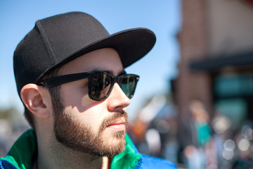 Portrait of young handsome man with black beard wearing dark sunglasses, cap and blue sleeveless jacket looking at the street on outdoor in the summer day