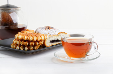 Tea and pastry on white wooden table