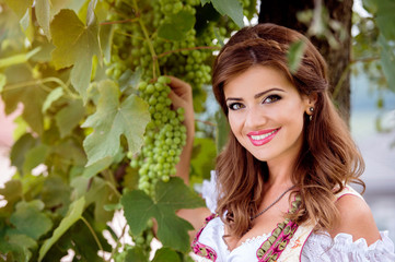 Beautiful young woman in traditional bavarian dress holding grap
