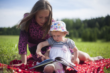 Two Sisters Reading a Book Outdoor