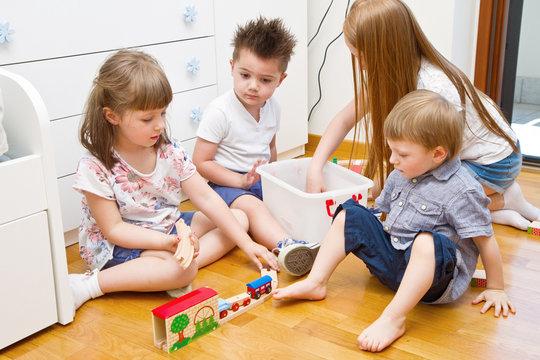 quattro bambini giocano in camera con il trenino