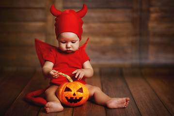 funny baby in devil halloween costume with pumpkin