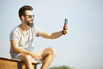 Handsome young man with beard taking selfie outdoor