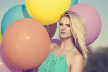 beautiful blonde happy woman with colorful pastel balloons in the city