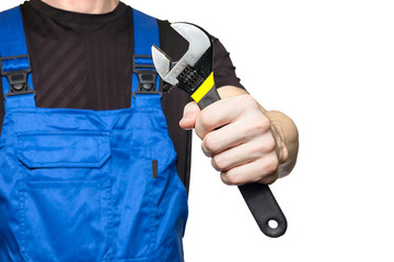 Man mechanic in working clothes holds a wrench in his hand isolated on white background