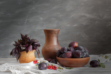 Still life in a rustic style: a set of pottery and plums on a wooden table