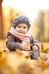 Kind in Ahornblättern