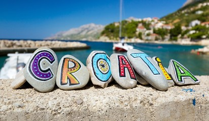 Croatia name painted on the stones, boat in marina in background