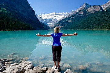 Woman in yoga pose meditating by water. Lake Louise in Canadian Rockies. Banff National Park. Alberta. Canada.