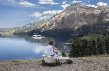 horizontal image of a lady sitting on a boulder and watching a boat glide by on the clear lake flanked by mountains.