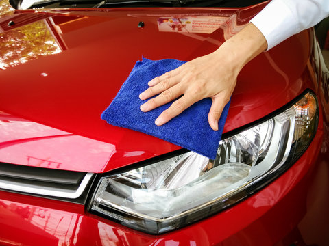 Selective focus hand with blue microfiber cloth cleaning red car.copy space.