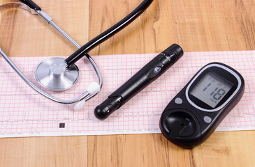 Glucometer with lancet device and stethoscope on electrocardiogram graph
