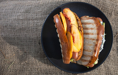 Hot dog with mango slices, avocado, lettuce and mustard on a black plate