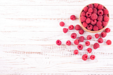 Ripe sweet raspberries in bowl on white wooden background. Copy space, top view