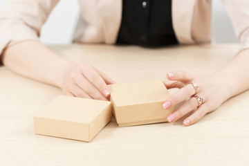 Woman holding two carton boxes on table. Female hands with post packages, preparing to open. Delivery service. online shopping, parcel opening concept