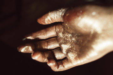 Beautiful hand in golden paint on black background close up. Gilded human palm, ceremonial greasepaint