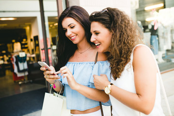 Beautiful young women having fun with smartphone in the street.
