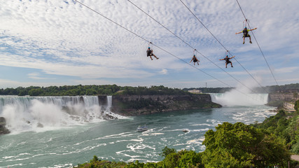 Wall Mural - Four unrecognizable people taking zipline ride at Niagara Falls, Ontario. New zipline in Niagara Parks opened in the summer of 2016