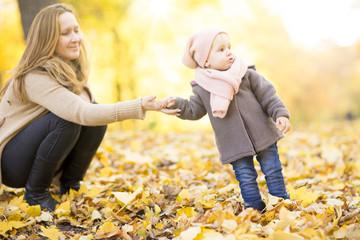 Mutter mit Tochter erste Schritte laufen lernen