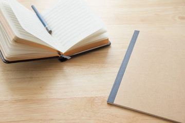 notebook papers with pencil on the wood table, work space, natural day light, selective focus