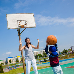 Mom and little boy son playing basketball