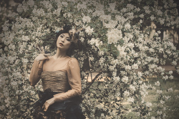 Asian woman in beautiful vintage dress posing on floral background