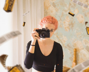 young girl with pink hair taking photo using film camera
