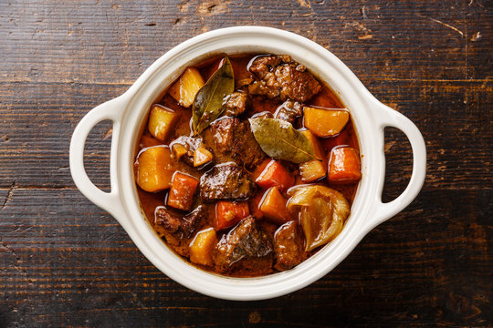 Beef meat stewed with potatoes, carrots and spices in ceramic po
