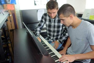 Two young men playing an organ