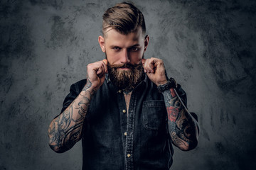 Bearded hipster with tattooe on his arms.