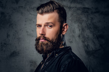 Bearded male in black shirt with tattoo on his neck.