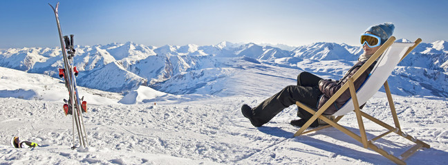 Panorama of a girl sunbathing in a deckchair near a snowy ski slope