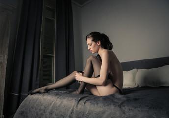 Sensual woman wearing stockings in her bedroom