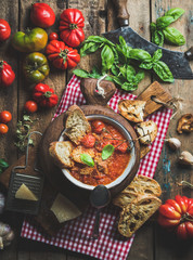 Homemade Italian roasted tomato and garlic soup in bowl on round serving board with basil, bread and Parmesan cheese over old rustic wooden background, top view, selective focus, vertical composition