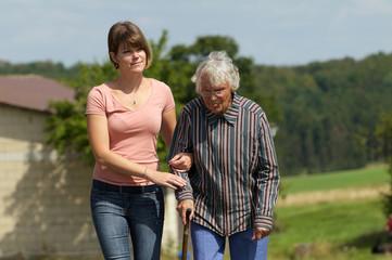 Junge Frau hilft Seniorin beim laufen