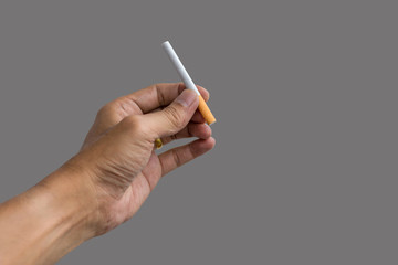 Man's hand holding a cigarette isolated on gray background.
