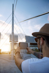 A young man shot from the back takes a photo of a cable bridge in a city on a summer evening