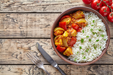 Chicken jalfrezi traditional homemade Indian spicy curry chilli meat with basmati rice and vegetables healthy dietetic asian food in clay dish on vintage table background.