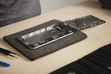 Close up on dissasembled drowned phone with removed battery and deattached screen in professional repairment lab