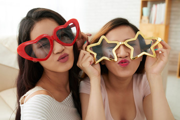 Two Asian happy girls in funny glasses looking at camera