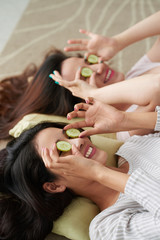 Pretty young girls enjoying cucumber masks together