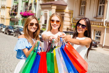 Three attractive girls in spectacles showing their purchases