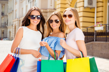 Three beautiful smiling women walking in the city with paperbags